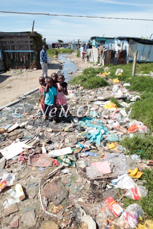 Children Play amongst rubbish in Khayelitsha, Cape Town's largest information settlement (township). Conditions for most residents are appalling despite legislative commitments to improve conditions. Caoe Town, South Africa.