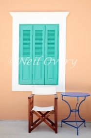 Shuttered window, chair and table, Kastellorizo, Greece