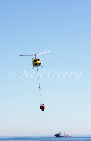 One of Cape Town's 'Working on Fire' Emergency Aerial Fire Fighting Helicopters collects water from the Atlantic Ocean off Sea Point, Cape Town, Western Cape, South Africa. 2015.