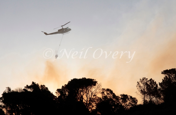 One of Cape Town's 'Working on Fire' Emergency Aerial Fire Fighting Helicopters with water bucket over a fire on Signal Hill, Cape Town, Western Cape, South Africa. 2015.