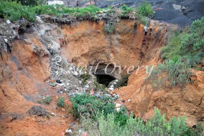Sink hole near people living near an abandoned coal mine slag heap, nr. Witbank, Mpumalanga, South Africa - such slag heaps often contain highly toxic heavy metals and pose a serious health risk. They are also supject to collapse.