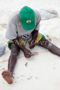 Fisherman repairs his net, Jambiani, Zanzibar