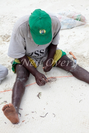 Fisherman repairs his net, Jambiani, Zanzibar